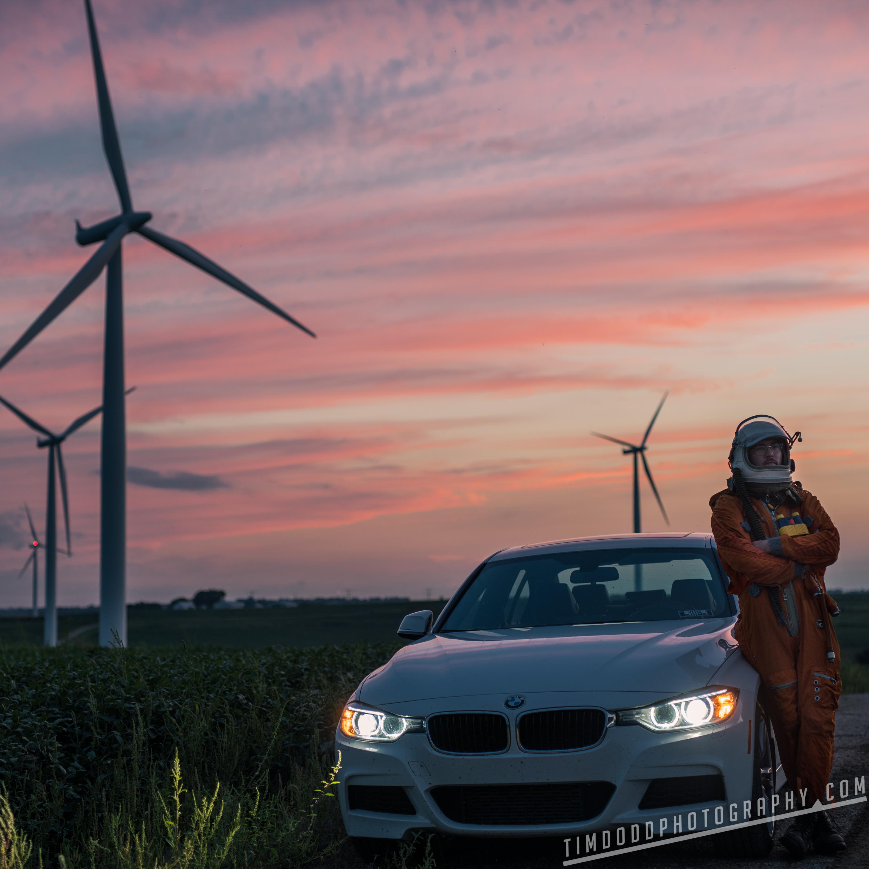 Astronaut BMW 328 I drive white sunset dusk windmill wind power turbine reusable renewable green energy space russian everyday astronaut Tim Dodd Cedar Falls Iowa Instagram viral Iowa corn fields